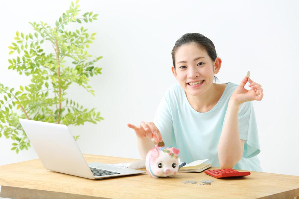 パソコンの前にいる女性が貯金箱にお金を入れて節約できている様子
