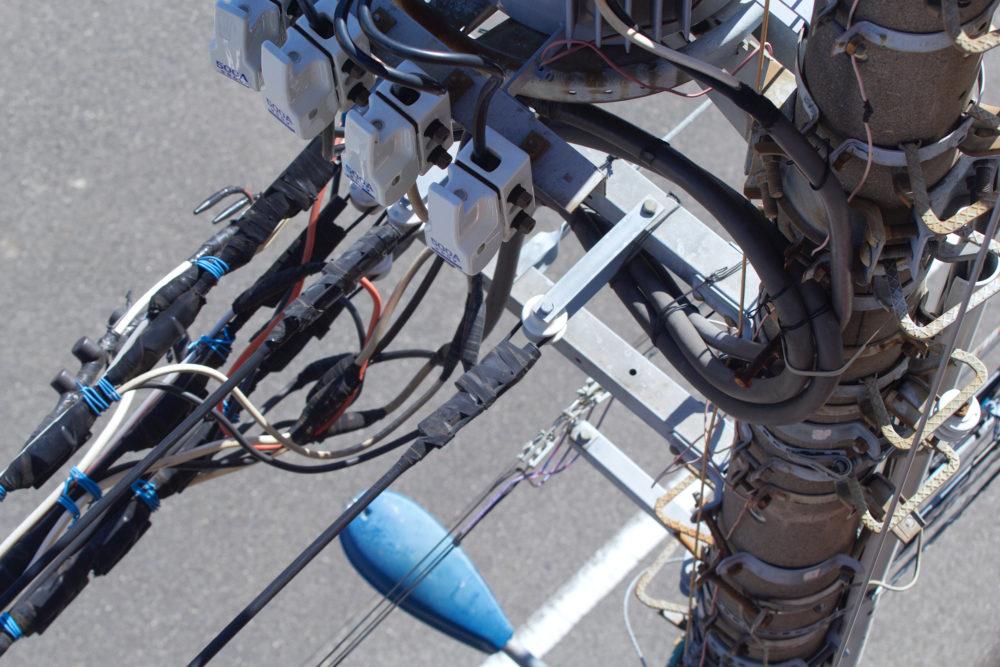電柱とその周辺の電話線や通信線の画像