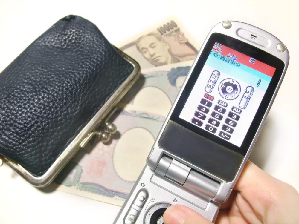 携帯電話と財布で出費をイメージする画像
