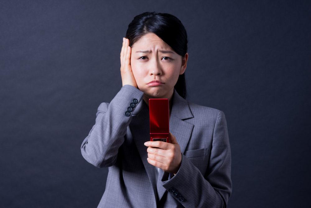 ガラケーが使えなくなって困っている女性の画像