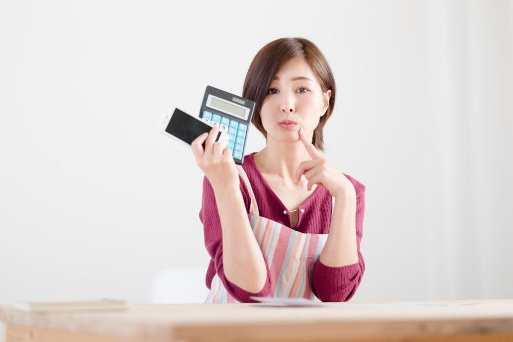 スマホ料金など家計を計算する女性