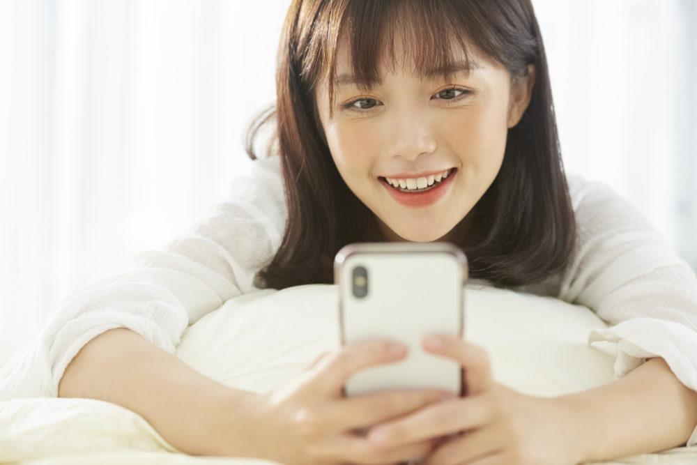 携帯電話料金の値下げ情報を読んでいる女性のイメージ